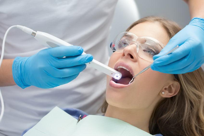 Zahnärztliche Kontroll Untersuchung, Junge Frau, die zu einer Kontrolluntersuchung in der Praxis Dres. Szostak ist